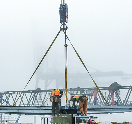 Workers and crane on foggy day