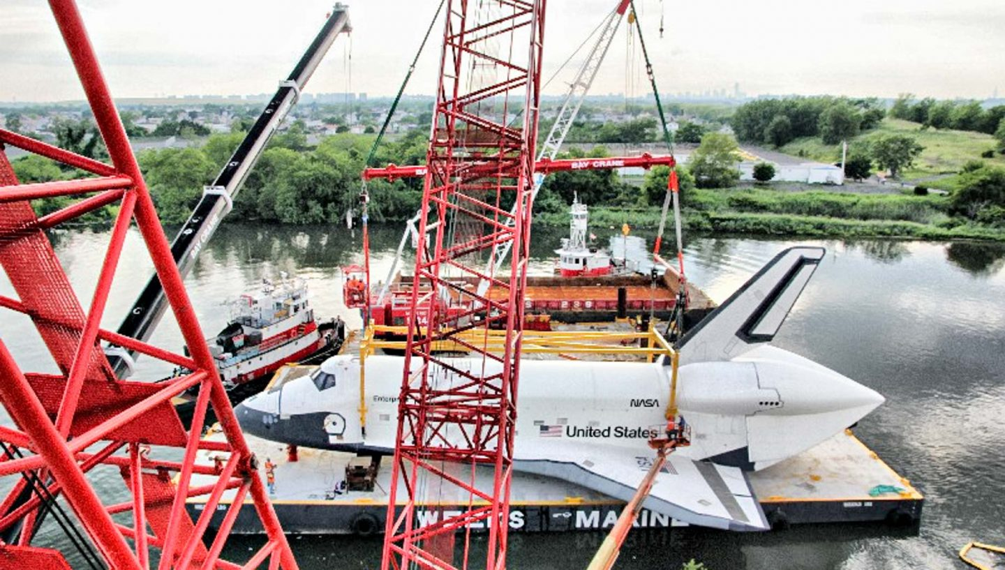 Cranes and space shuttle on river