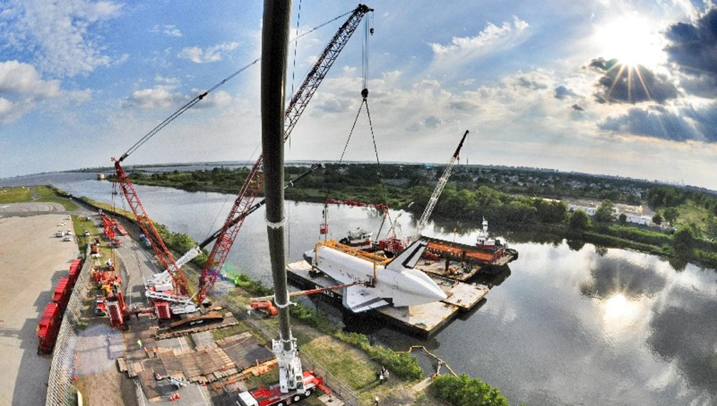 Crane lifting space shuttle onto river platform
