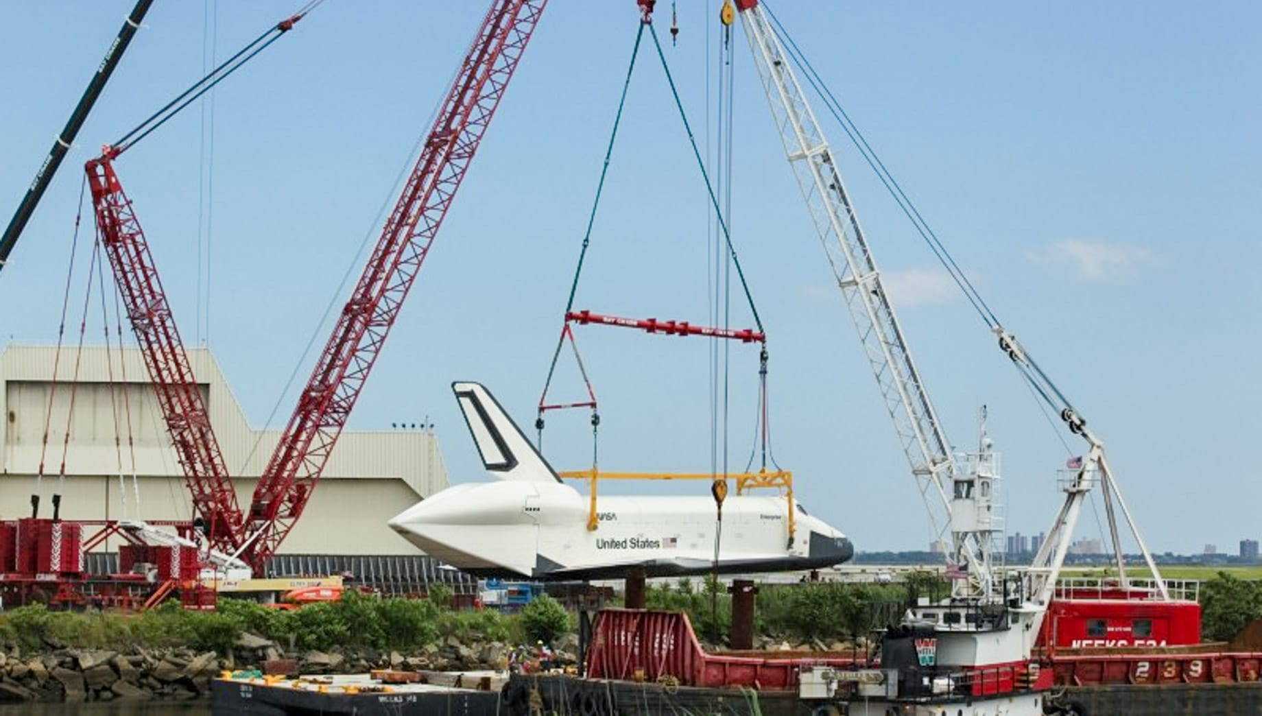 Cranes lifting space shuttle onto river platform